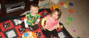 Little brother and big sister enjoy an indoor picnic
