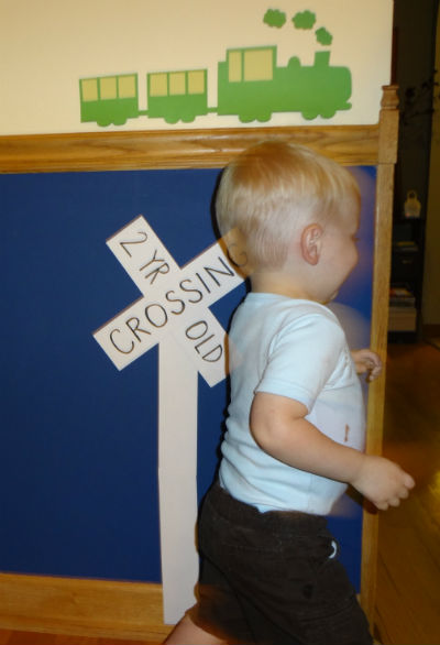 2 yr old running by 2 year old crossing sign