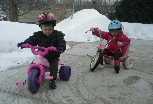 Riding trikes on the patio surrounded by snow