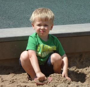 little brother playing in the sand