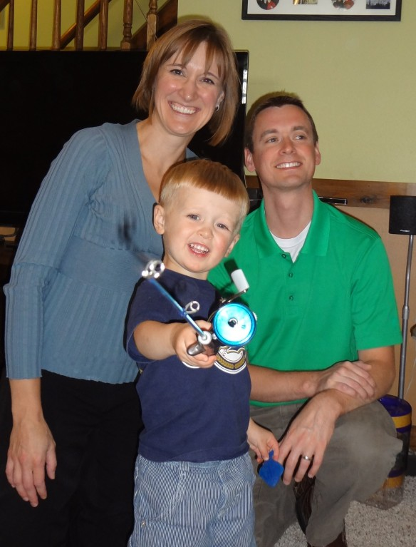 Little brother turns 3 - showing off his fishing pole with Mom & Dad.