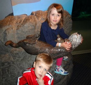 Big sister cradling the otter by their exhibit. Little brother not interested in smiling...